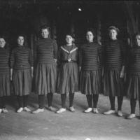 Sju elever fra Jæren Folekhøgskule i gymna- stikkdrakt. En ribbevegg i bakgrunnen.