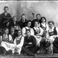 Elever fra Jæren Folkehøgskole. Kvinner med hardangerbunad. Mann bak i midten i Setesdalsbunad
