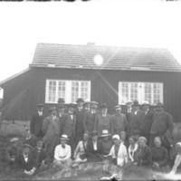 Arne Garborg - til høyre for midten - sammenmed en gruppe menn og kvinner. Utenfor Knudaheio.