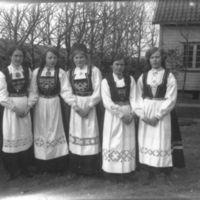 Fem elever fra Jæren Folkehøgskule i  hardangerbunader i K.K. Kleppes hage.