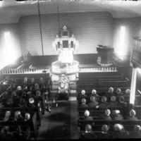 Blomstersmykket kiste i Klepp kirke.  Folk i benkeradene - kvinnene til venstre ogmennene til høyre.