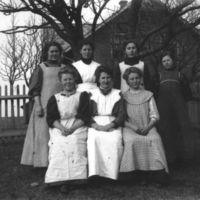 Sju jenter (elever el. kjøkkenjenter?)utenfor Jæren Folkehøgskule. K.K. Kleppes hus i bakgrunnen.